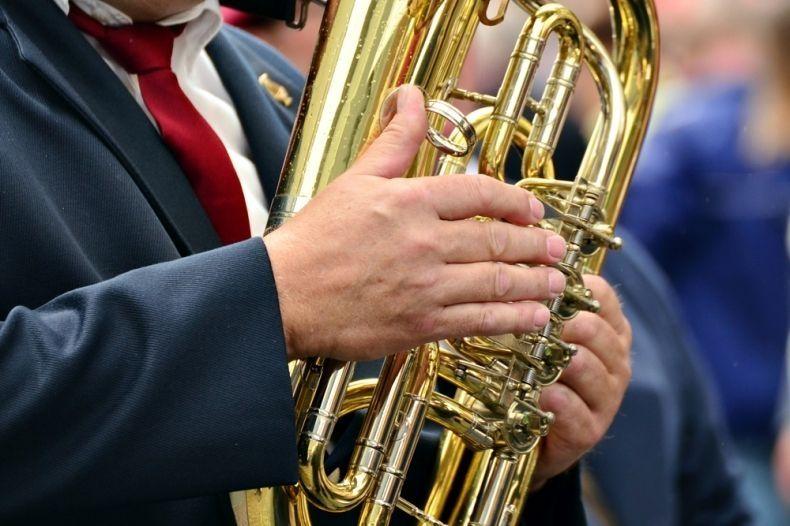 Mężczyzna trzyma w dłoniach instrument dęty