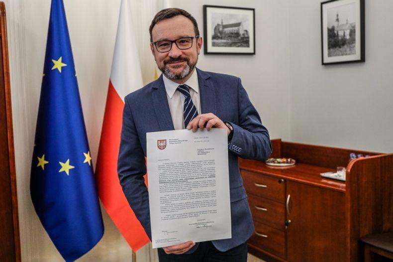 Wicemarszałek Tomasz Urynowicz trzyma pismo. W tle flagi Polski i Unii Europejskiej.