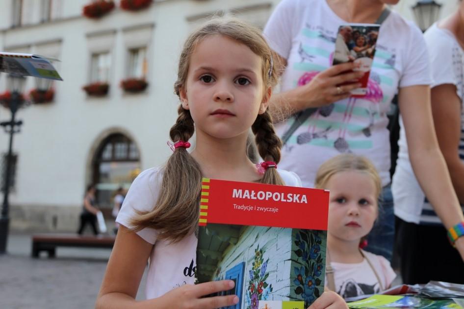 Zdjęcie przedstwia dziewczynkę zpublikacją oMałopolsce wręce
